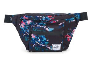 """Made from a water-resistant polyester, this classic hip pack from Herschel is young and fresh with its """"floral blur"""" pattern. Two zip pockets and an adjustable web strap add utility and comfort."""