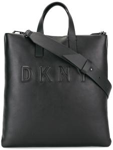 This DKNY black leather tote features a magnetic closure, top handle and adjustable strap. The boxy design takes this bag from tough to tomboy chic.