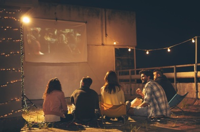 Friends watching a movie on a building rooftop terrace