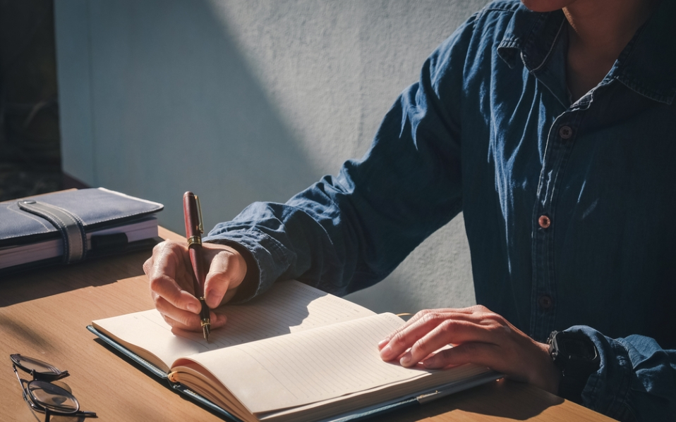 man writing journal