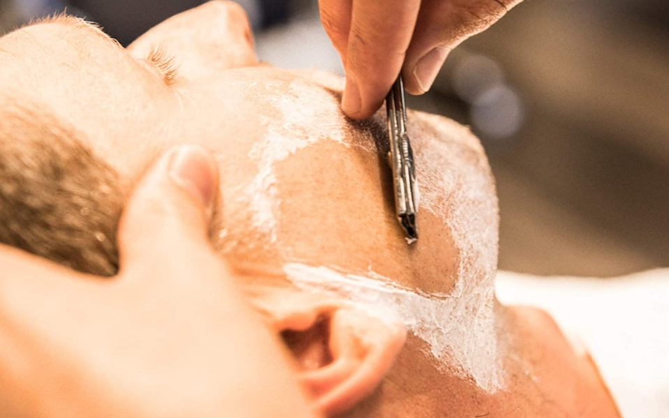 Barber shaves a man's face using