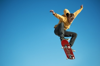 A teenager skateboarder does an ollie trick on background of blue sky gradient