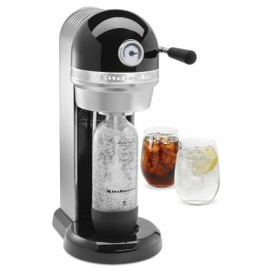 a kitchenaid sparkling beverage maker in black with two glasses of soda