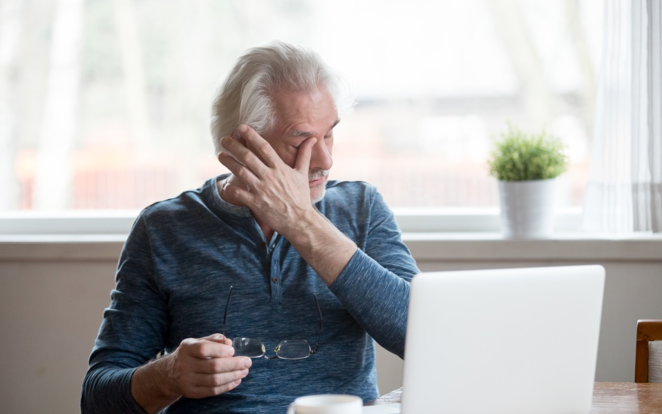 Fatigued mature old man taking off