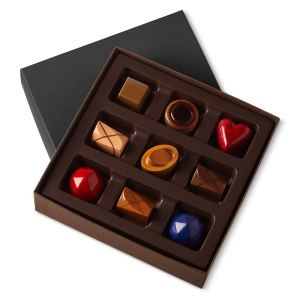 a box of nine colorful chocolates on top of its lid on a white background