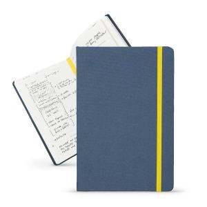a thebestselfco. planner with a blue cover and a yellow band in front of an open planner on a white background