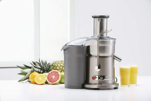 a breville juicer making two cups of citrus juice while being displayed on a white countertop next to grapefruits, lemons and a pineapple