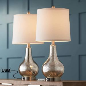 two ledger lamps with silver bases sitting on a table next to a blue wall