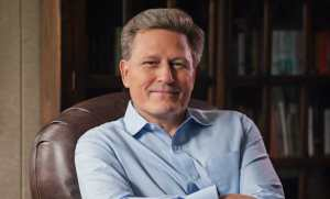 david baldacci sitting in a leather armchair and looking at the camera