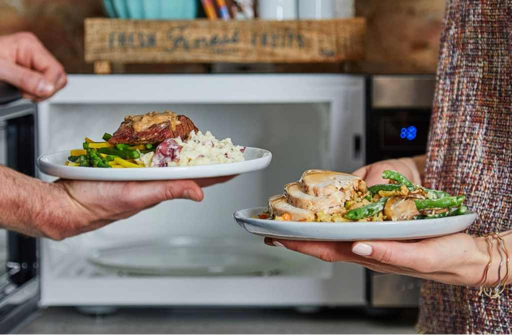 two people holding plates of food in front of a microwave