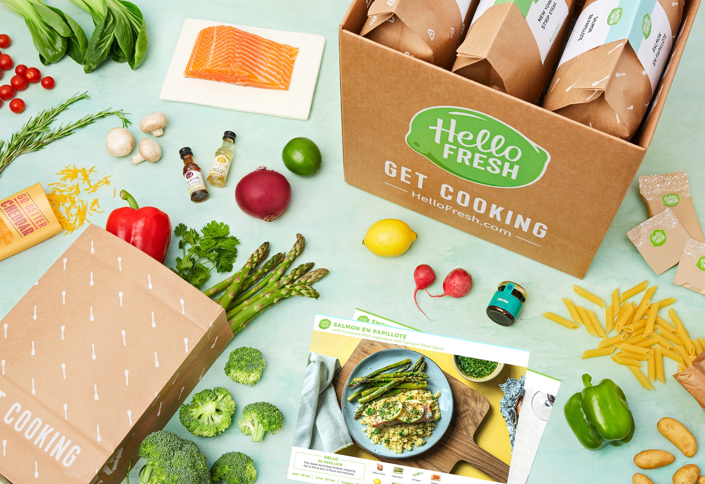 a hello fresh box on a table alongside a bag of vegetables, fish and a recipe card