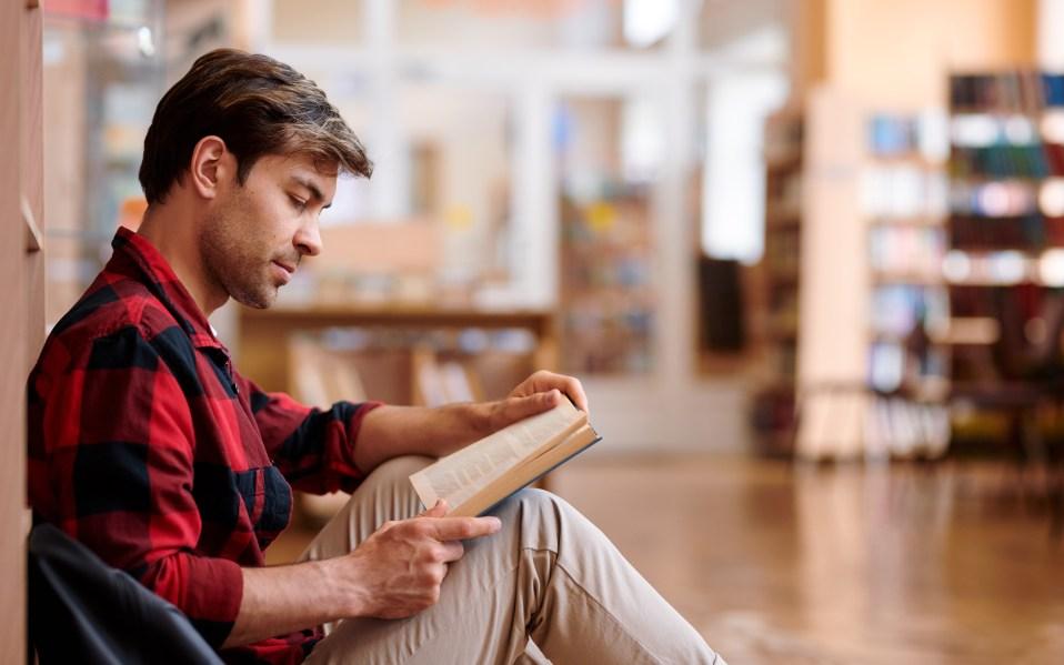 man sitting near a book shelf