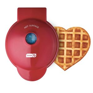 a red heart waffle maker with a heart-shaped waffle sitting next to it on a white background, best waffle makers