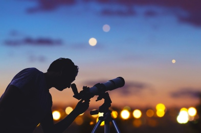 Astronomer with a telescope watching at the stars and Moon. My a