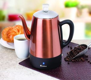 a copper electric coffee percolator sitting on a kitchen counter next to a cup of coffee
