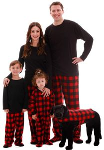 a family of a man a woman a little boy a little girl and a dog wearing black shirts and red plaid pants on a white background