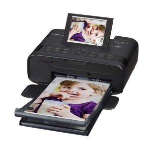 a canon mini photo printer with its lcd screen showing a photo of a young girl eating. the printer is printing the same photo to the front of the picture
