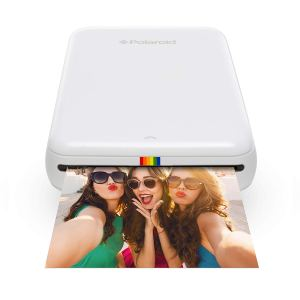 a polaroid instant photo printer printing a photo of three girls on a white background