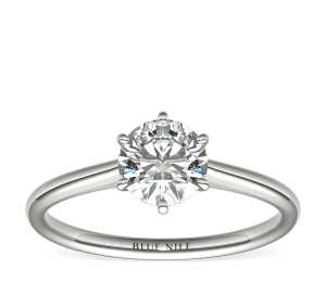 petite nouveau solitaire engagement ring on a white background
