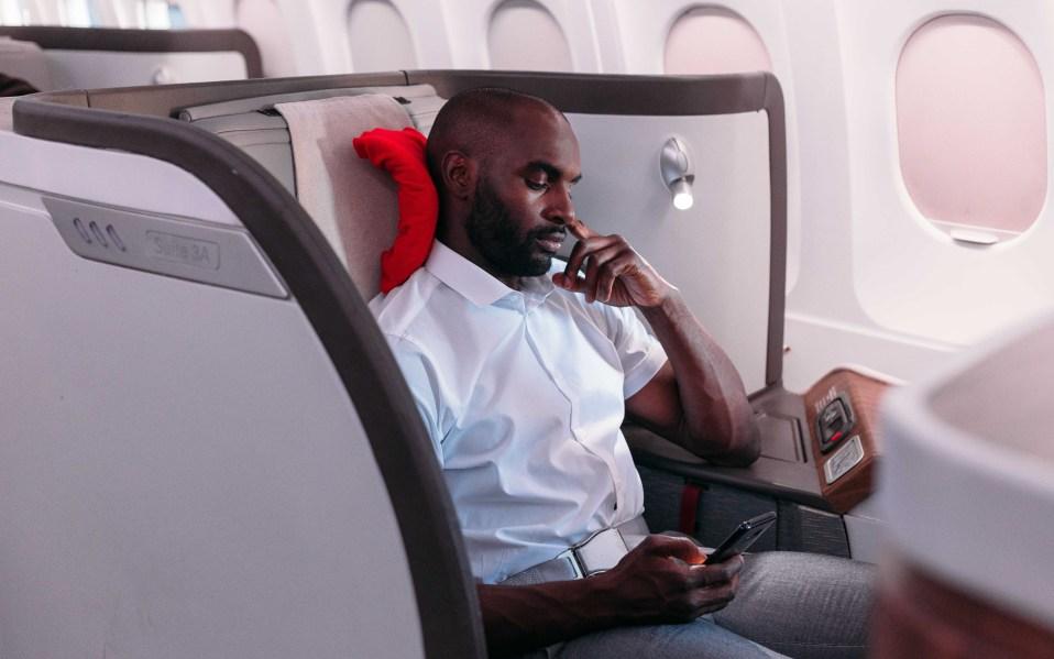 man wearing trtl pillow on plane