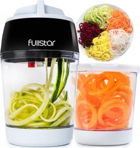 a fullstar zucchini noodle maker with a cup full of zucchini noodles and a cup of spiral carrots alongside a plat of cut vegetables on a white background