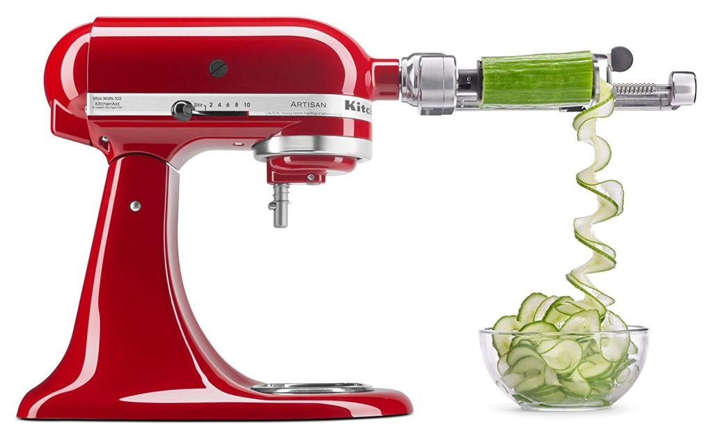a red kitchenaid mixer with a spiralizer attachment on the front cutting cup a cucumber
