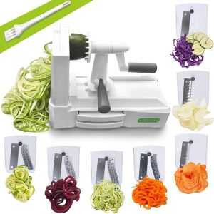 a spiralizer and its seven attachments with several vegetables cut up on a white background
