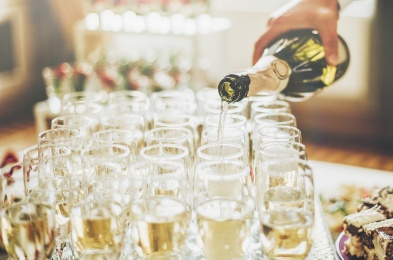 waiter pouring champagne in stylish glasses at luxury wedding reception. rich celebration. expensive catering and service at feast. new year and christmas celebrations and drinks
