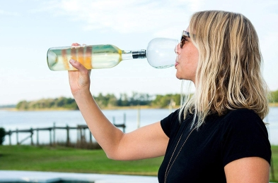 Woman Drinking from Wine Glass Attached to Wine Bottle