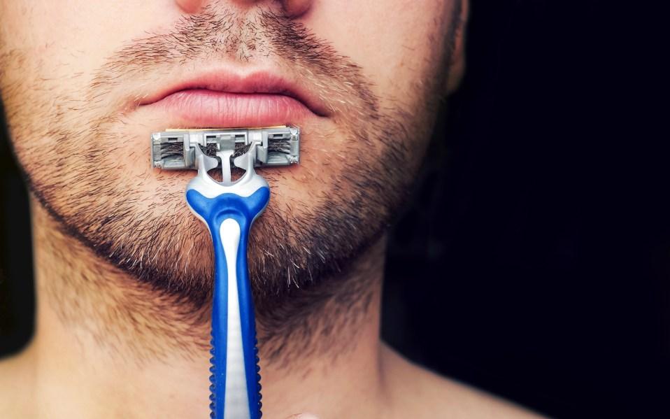 man holding gillette razor on face