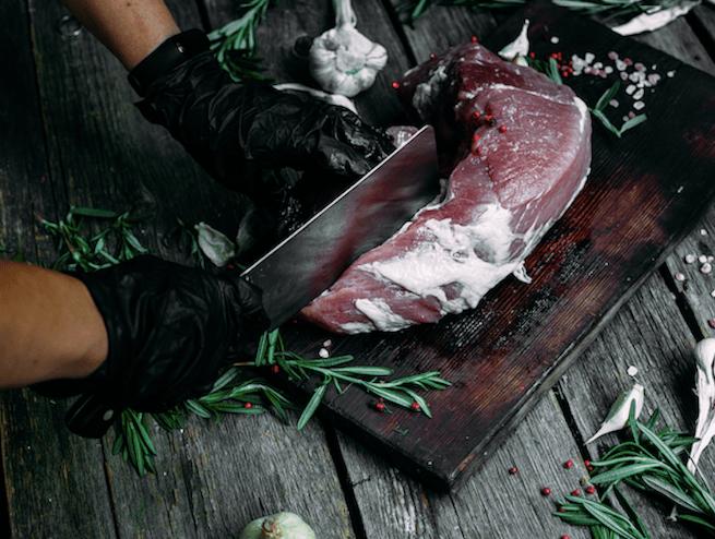 man's hands preparing pork chops