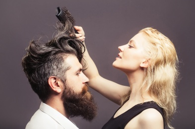 blonde hairdresser combing bearded man