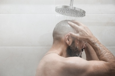A man washes in the shower. Side view.