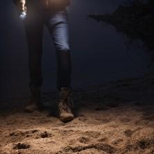 Man with flashlight walking at riverside, closeup