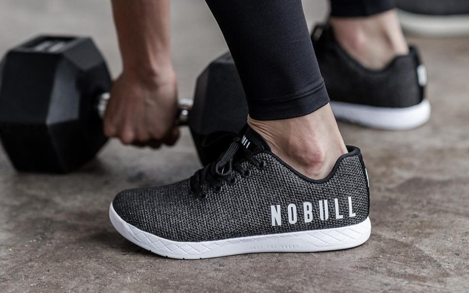 Person lifts dumbbell while wearing NOBULL