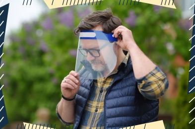 Man putting on face shield on street of city or public park. Safety during COVID-19 outbreak. Lifting virus lockdown. Social distancing and face mask - security measures when exiting quarantine.
