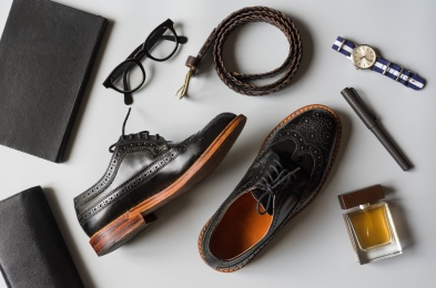 Top view of men leather shoes and accesories in black tone, wingtip shoes on grey background
