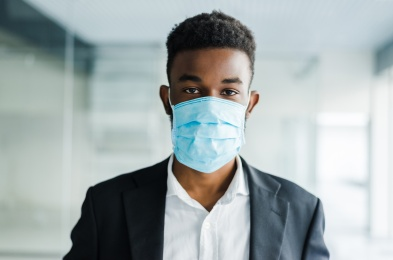 Young african man in medical mask on his face in office
