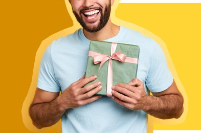 handsome bearded overjoyed man holding a gift