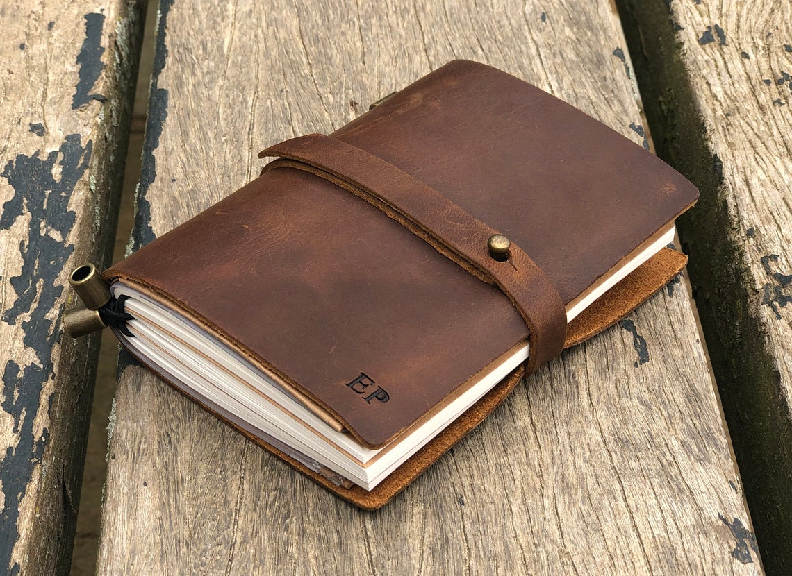 Personalized Leather Notebook rests on a wood table
