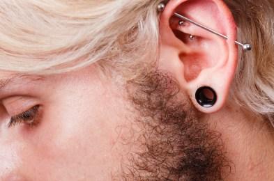 Pierced man ear, black plug tunnel, industrial and rook
