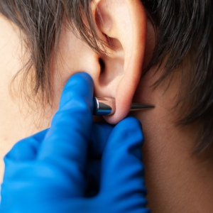 piercing and stretching the ears with medical blue gloves. incr