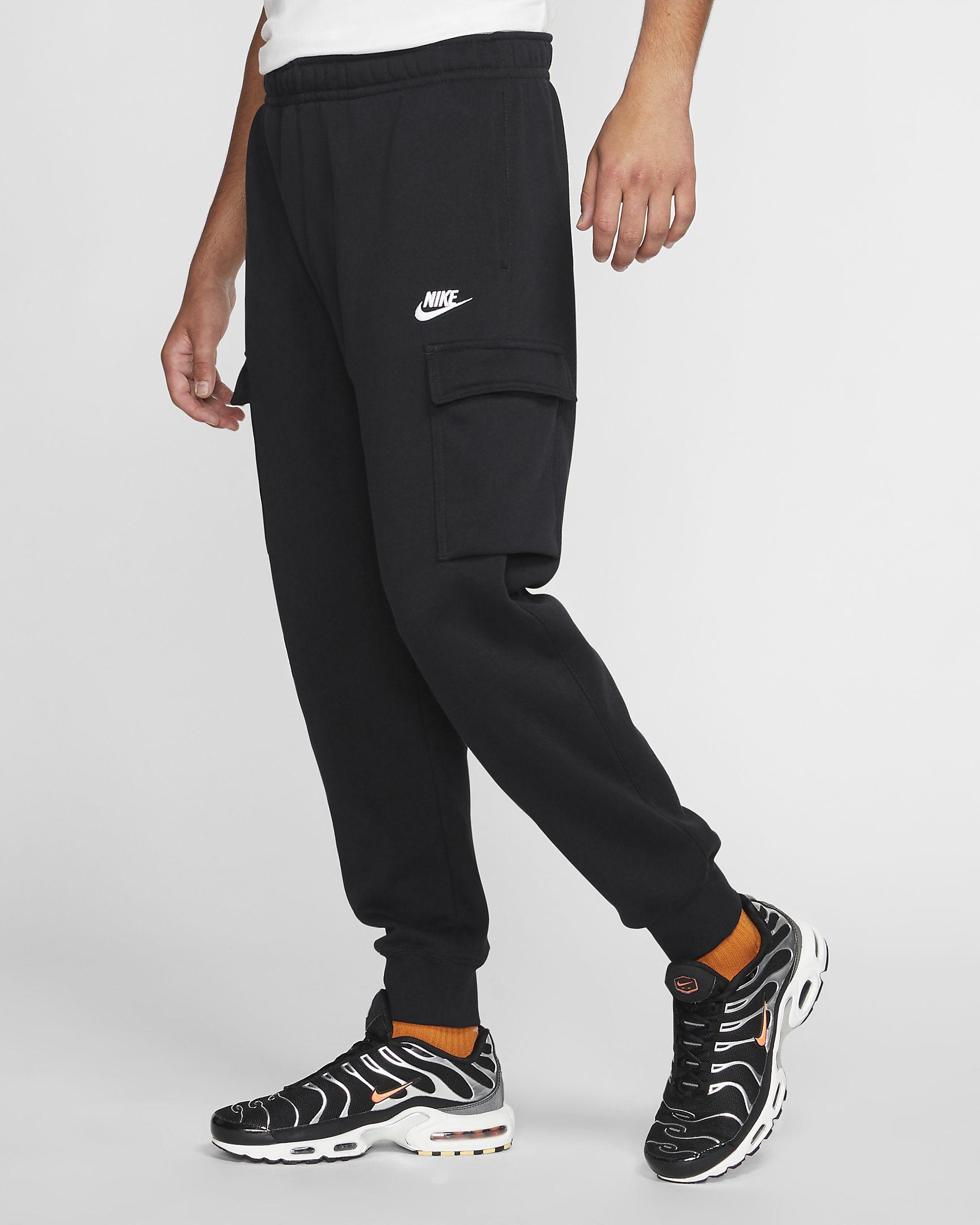 Man wears black Nike Sportswear Club Fleece Cargo Pants with Nike sneakers