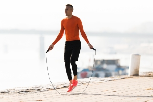 man exercising by using a weighted jump rope