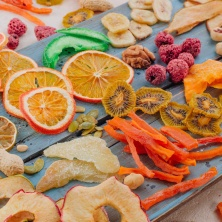 Mixed dried fruit and vegetable chips, candied pumpkin slices, nuts and seeds on blue wooden board