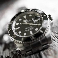 Close-up, abstract and shallow focus view of an iconic, swiss-made men's automatic divers watch showing the ceramic bezel and famous cyclops date lens.