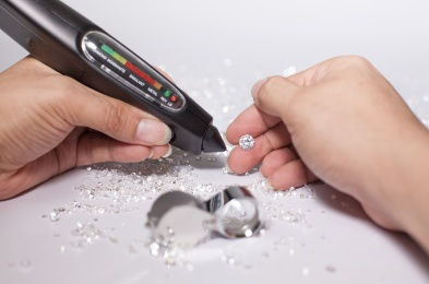 Diamonds in front of a white background, reflections on the ground. brilliant cut diamond held by right hand, diamond testing machine, tester, white gemstone, diamond checking equipment.