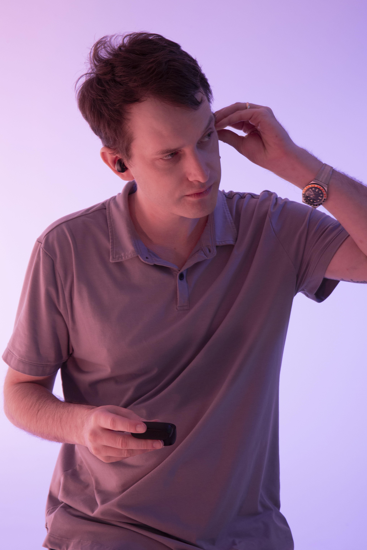 male model placing earbuds in ear, 2020 man awards