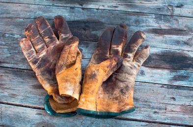 Yellow dirty work gloves on a wooden table stained with grease a