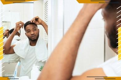 Young black man examining his hair, looking at bathroom mirror